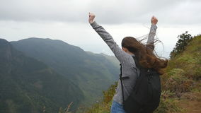 Young female hiker with backpack reaching up top of mountain and raised hands. Woman tourist standing on the edge of stock footage