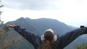 Young female hiker with backpack reaching up top of mountain and raised hands. Woman tourist standing on the edge of stock video footage