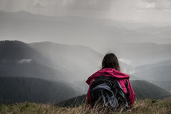 Traveller on trekking trip to mountains rests at mountain area and looks at heavy thunder rain pouring nearby. Young female hiker with backpack sits in grass on Stock Photography