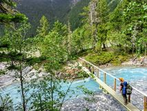 A young female hiker carefully crossing a small skinny wooden bridge over a narrow electric blue rushing river. In the remote forests of Mount Robson Provincial stock photo