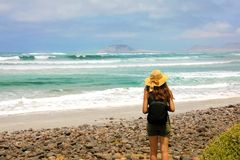 Young female hiker discovering wild paradisiac beach in Lanzarote Island. Back view traveler girl arrives on hidden amazing beach stock photo