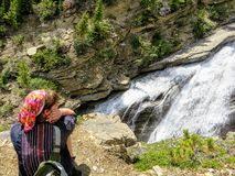 A young female hiker at the edge of the cliff looking down at the rushing waters of Toboggan Falls. Below along the Berg Lake Trail in Mount Robson Provincial stock image