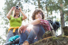 Young female hiker photographing through digital camera while man looking away in forest. Young female hiker photographing through digital camera while men Stock Photos
