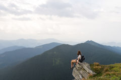 Young female hiker sits on rock in gorgeous mountain area and looks in endless horizon Royalty Free Stock Photos