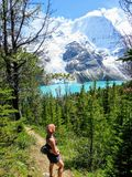 A young female hiker stopped along a hiking trail admiring the beautiful and incredible view of a lake and glacier royalty free stock images