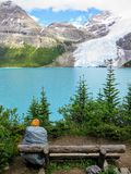 A young female hiker stopped along a hiking trail admiring the beautiful and incredible view of a lake and glacier royalty free stock photos