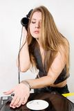 Young female hip-hop dj scratching. Attractive girl plays vinyl record on turntable Royalty Free Stock Images