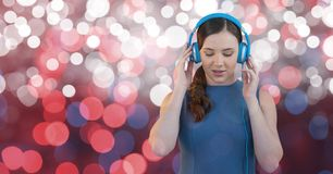 Young female hipster listening to music on headphones against bokeh Royalty Free Stock Image