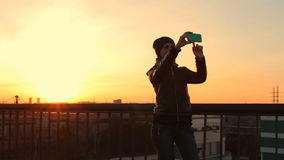 Young female hipster making selfie on mobile phone at bridge sunset city view stock footage