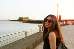 Young female hipster traveler with sunglasses and backpack looking at camera near the beach with sunset flare Royalty Free Stock Photos