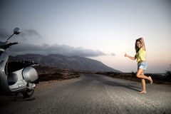 Young female hitchhiking alone in the countryside Royalty Free Stock Photos