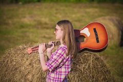 Young female holding acoustic guitar over her shoulder on the me stock image