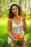 A young female holding apple. Beautiful young girl in the summer forest Stock Photos