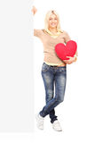 Young female holding a blank panel and red heart. Full length portrait of a young female holding a blank panel and red heart against white background royalty free stock photos