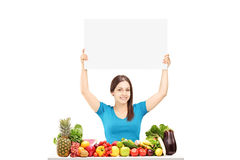 Young female holding a blank panel and sitting on a table with f Royalty Free Stock Photos