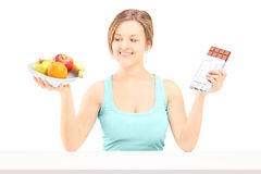 Young female holding a bowl of fresh fruit and chocolate, trying Royalty Free Stock Photos