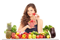 Young female holding a bowl of strawberries and posing behind a Stock Photography