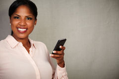 Young female holding a cellphone while smiling Stock Images