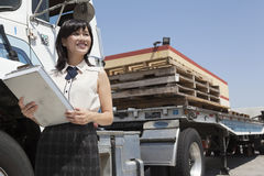 Young female holding clipboard while standing next to flatbed truck Royalty Free Stock Image
