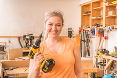 Young female holding drill and smiling towards camera Royalty Free Stock Image