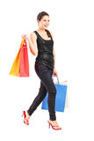 Young female holding shopping bags and walking Stock Photography
