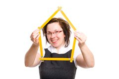 Young female holds measure in shape of house Royalty Free Stock Photography