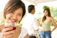 Young female host toasting. Viewers with a glass of drink, with her friends in background Stock Image
