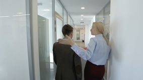 The young female HR manager is showing the office of financial company to the new male employee. The businessman and woman with red folder are going throught stock video footage