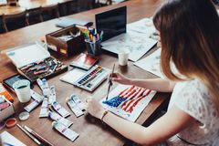 Young female illustrator drawing flag of the USA in using aquarelle paint sitting at workplace.  Royalty Free Stock Photography