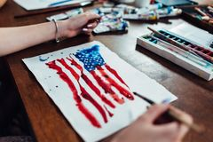Young female illustrator drawing flag of the USA in using aquarelle paint sitting at workplace.  royalty free stock photos