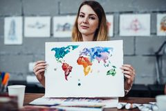 Young female illustrator showing her painting drawn with watercolor technique in her studio.  Royalty Free Stock Image