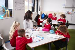 Young female infant school teacher sitting at a table in a classroom with her pupils stock images