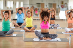 Young female instructor doing yoga exercises. Young curly female instructor doing yoga exercises with group in gym royalty free stock image