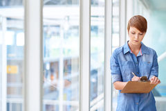 Young female intern taking notes on clipboard next to windows Stock Photography