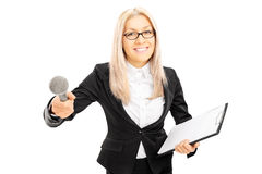 Young female interviewer holding clipboard and microphone Royalty Free Stock Image