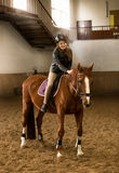 Young female jockey siting on brown horse in riding hall Royalty Free Stock Photo