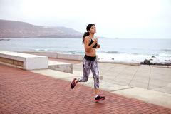 Young female jogger on the esplanade. Young girl jogging on a paved esplanade close to a seashore, wearing casual clothes, running shoes and her hair tied back Stock Images
