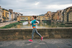 Young female jogger with headset is running by Arno riverside Royalty Free Stock Photos