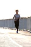 Young female jogger running outdoors Stock Photos