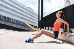 Young female jogger suffering from pain outdoor. Upset girl feels cramp of body after training. She is leaning arms on border and trying to relax. Her eyes are Royalty Free Stock Image