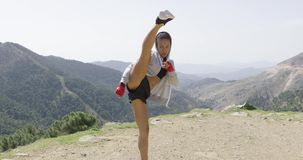 Young female kickboxer in mountains stock footage