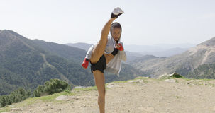 Young female kickboxer in mountains Stock Image