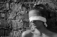 Young female kidnapping, woman abuse. Black and white portrait of a young woman laying on a brick wall with a scarf on her eyes Stock Photo
