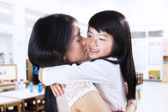 Young female kissing her daughter Stock Photography