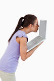 Young female kissing laptop screen Stock Photo