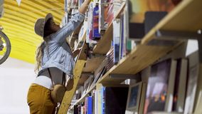 Young female on ladder in library. Bottom view of young woman on high ladder choosing books on shelf in bookstore with decorative bicycle hanging under roof in stock video