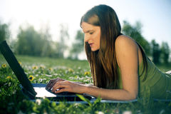 Young female with laptop. Portrait of a cute young female lying on the grass in the park using a laptop Y Royalty Free Stock Photography