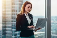 Young female lawyer working in her luxurious office holding a laptop standing against panoramic window with a view on. Business district stock photography