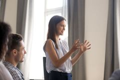 Young female leader, businesswoman, coach holding company briefi. Ng, talk to colleagues, training interns at company meeting, discuss business strategy royalty free stock image