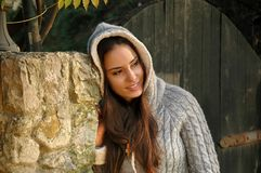 Young female leaning head on stone column, with hood on Royalty Free Stock Images